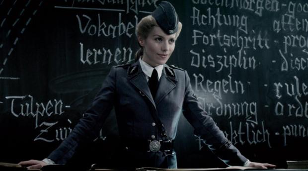 """Kuva 13. Kuunatsien oppitunnilla käytetään opetusmateriaalina Diktaattori-elokuvaa. """"Mitä tästä opimme, lapset?"""", utelee Renate Richter (Julia Dietze)."""