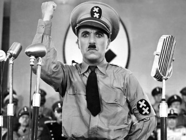 """Kuva 4. Charlie Chaplinin unohtumaton puhekohtaus elokuvassa Diktaattori (1940). Adenoid Hynkel vetää mahtailevan puheen käsittämättömällä siansaksalla ja uutiskatsauksen toimittaja """"tekstittää"""" puheen sisällön. © Warner Home Video / Charles Chaplin Film Corporation."""